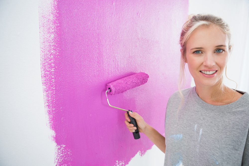 Pretty blonde painting her wall pink and smiling at camera in new home