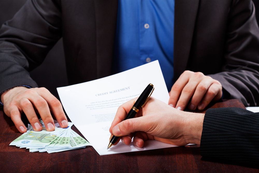 A closeup of a man signing an express cash loan agreement