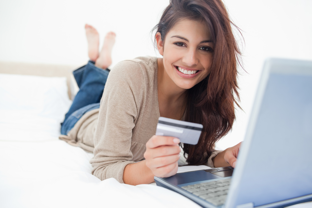 A woman smiling and looking in front of her as she uses her credit card with her laptop.-3