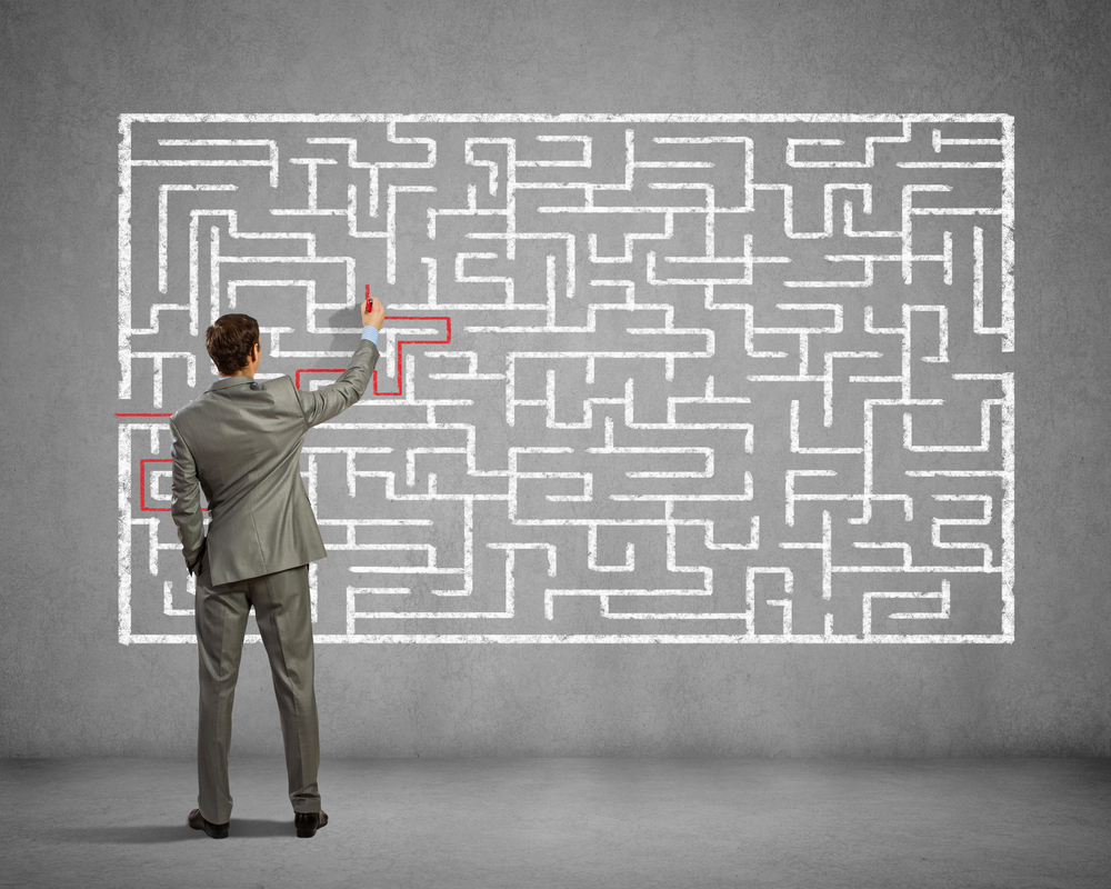 Back view image of young businessman trying to find way out of maze
