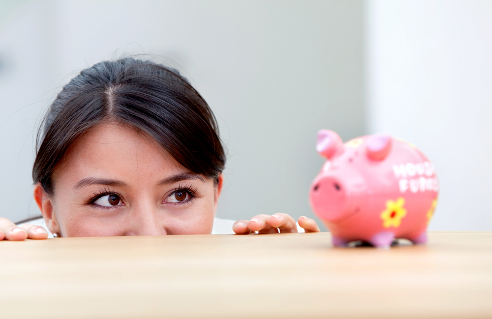 Business woman at the office looking at a piggybank on the desk