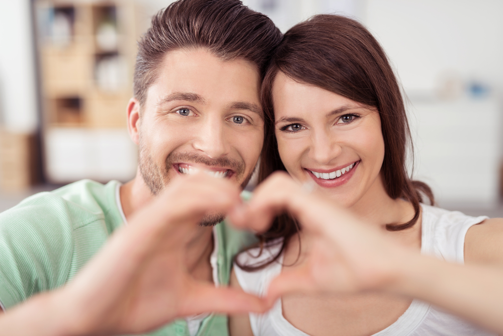 Close up Happy Sweet Young Couple at the Living Room Showing Heart Shape using Hands and Smiling at the Camera.