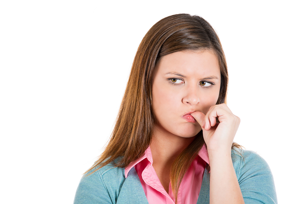 Closeup portrait of envious unhappy, upset miserable woman, biting fingernail, looking sideways, isolated on white background. Negative human emotions, facial expressions, feeling, attitude, behavior