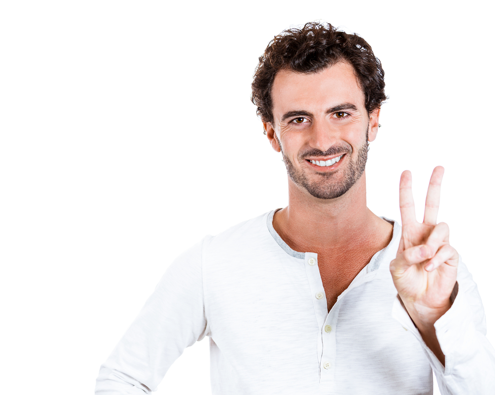 Closeup portrait of happy, excited successful young man giving peace, victory or two sign, isolated on white background. Positive emotions, face expressions, feelings, attitude, reaction, perception