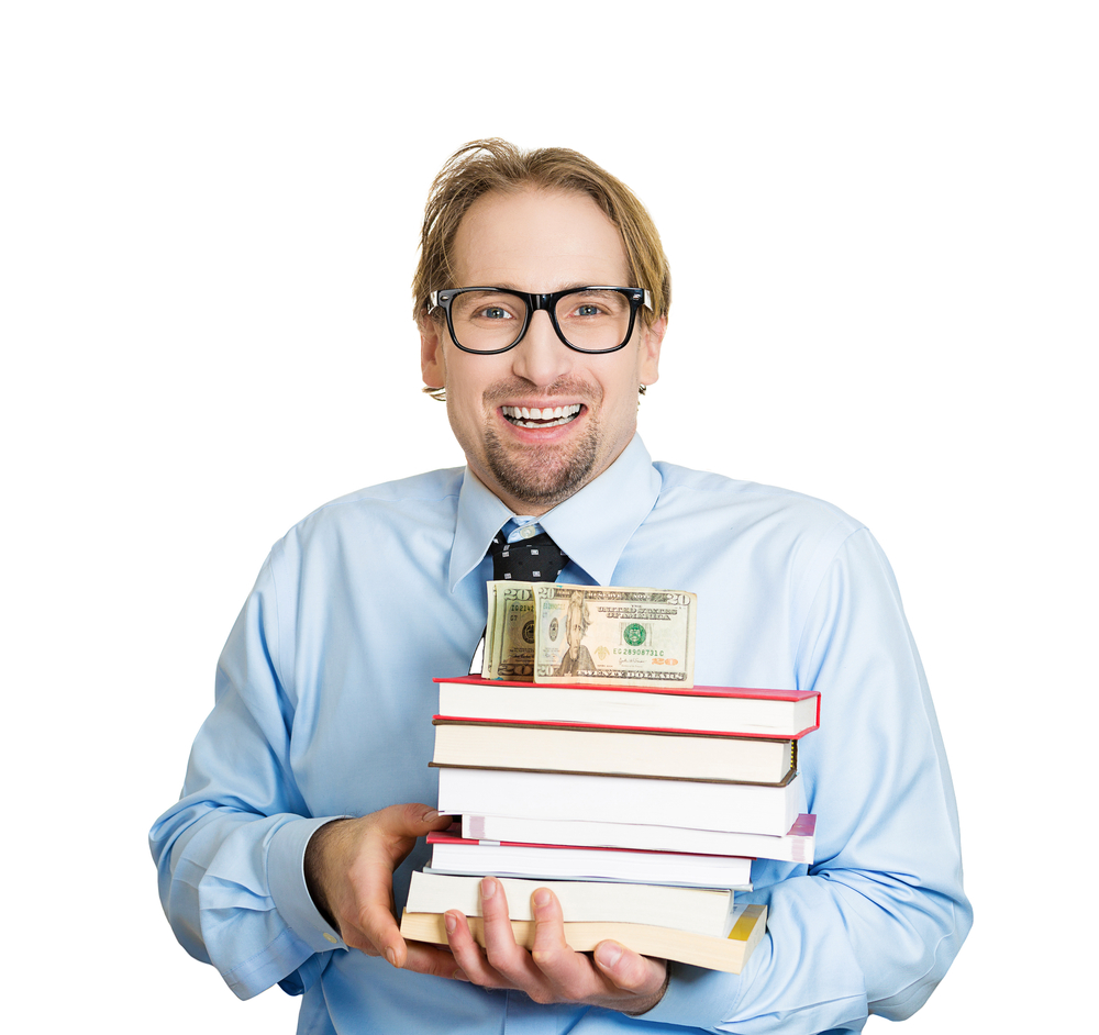 Closeup portrait of young smiling student man holding books in arms with money, cash on top, looking happy, scholarship fund or selling textbooks, isolated on white background. Education value