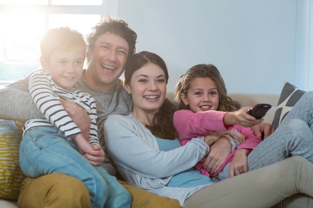 Family watching television while sitting on sofa at home