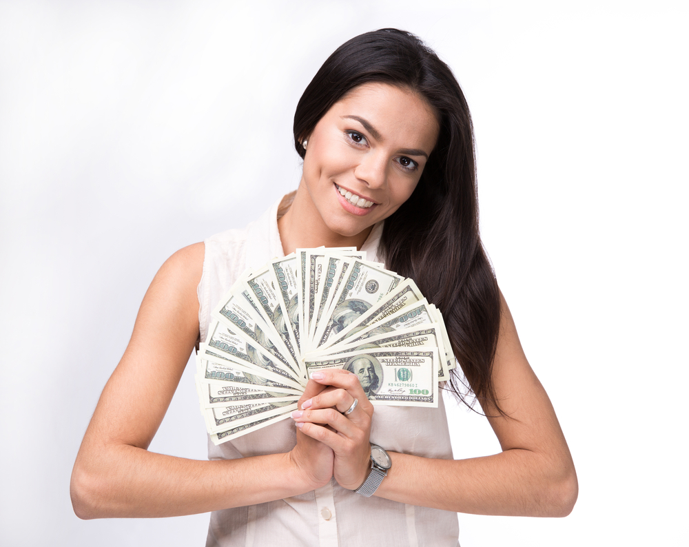 Happy woman holding US dollar bills over white background and looking at camera