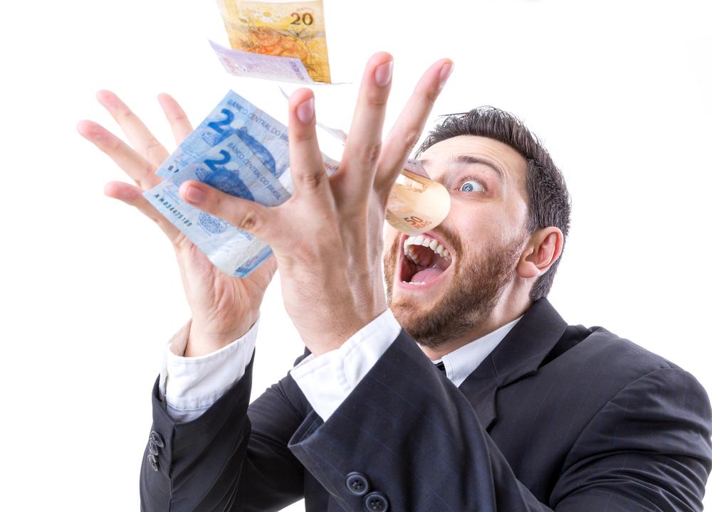 Happy young man in a rain of Brazilian Money