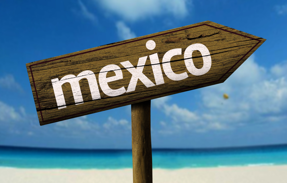 Mexico wooden sign with a beach on background