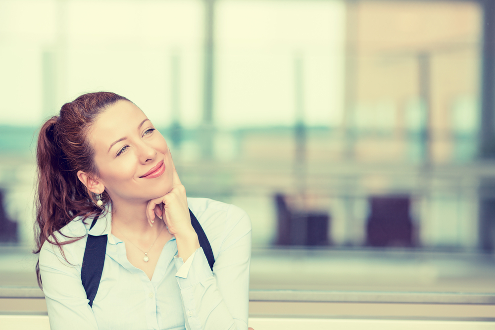 Portrait happy young woman thinking dreaming has many ideas looking up isolated office windows background. Positive human face expression emotion feeling reaction. Decision making process concept-1