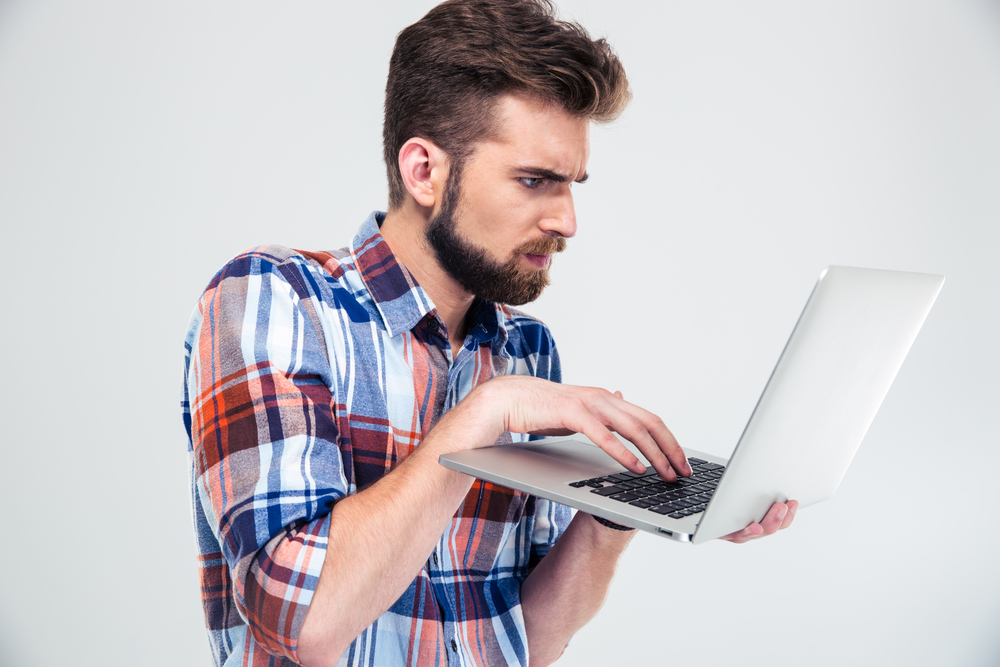 Serious young man standing and using laptop isolated on a white background