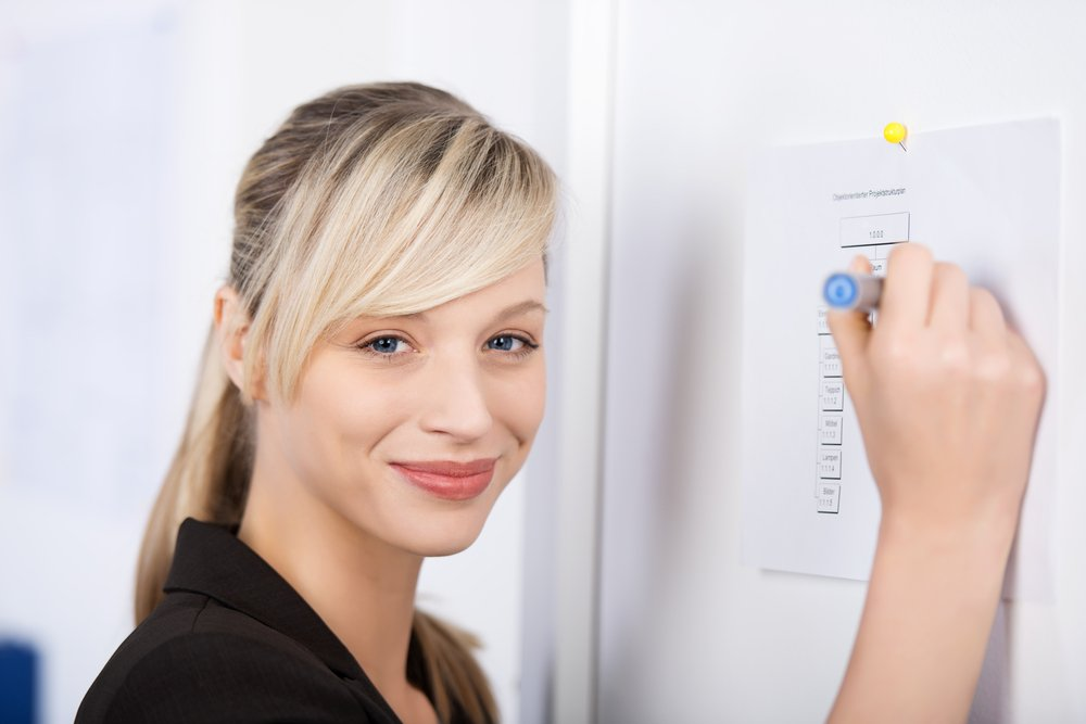 Smiling businesswoman writes something on the wall