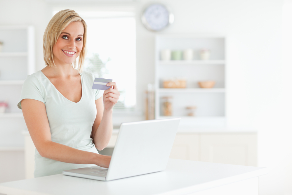 Woman with credit card and notebook looks into camera in the kitchen