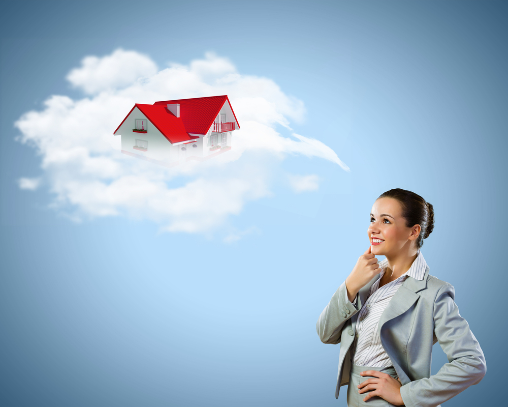 Young pretty businesswoman with houses over head