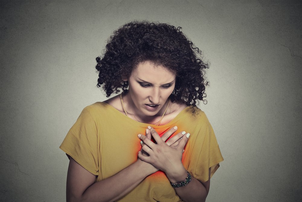 sick middle aged woman with heart attack, pain, health problem holding touching her chest colored in red with hands isolated on gray wall background. Human face expression